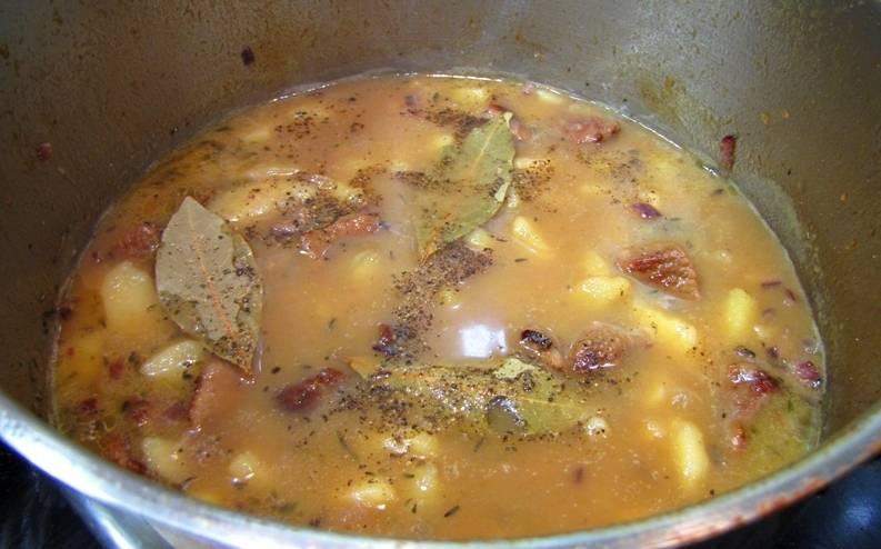 Теперь аккуратно достаем кастрюлю из духовки и добавляем в нее обжаренный лук, лавровый лист, специи и соль по вкусу. Возвращаем кастрюлю в духовку еще на 5-10 минут. Затем опять достаем ее и посыпаем мясо с картофелем измельченной петрушкой. На 20 минут ставим кастрюлю в выключенную духовку, даем блюду настояться.