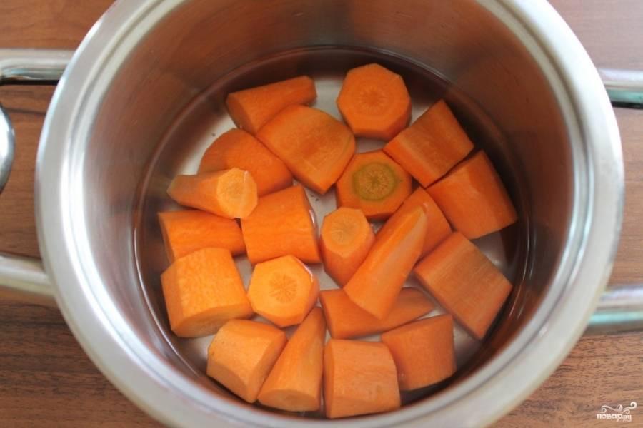 Морковку почистите и порежьте кусочками. Выложите в кастрюлю, залейте водой и поставьте вариться до готовности.