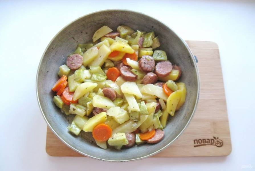 Выложите овощи с колбасками на противень или в глубокую сковороду. Отправьте в духовку, разогретую до 190-200 градусов и запекайте до готовности 35-40 минут.