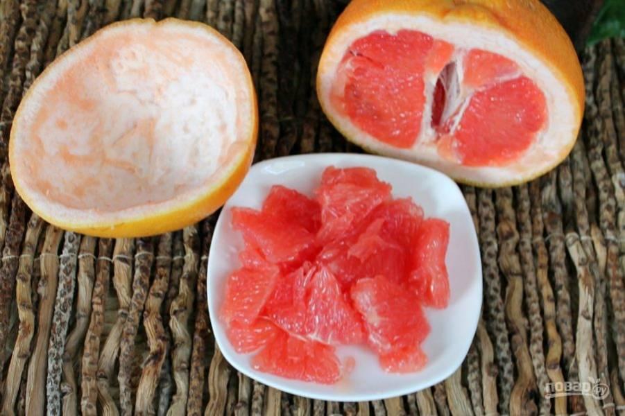 Грейпфрут разрезаем пополам. Мякоть аккуратно вынимаем, чтобы остались целыми шкурки, в которых будем подавать салат.  Дольки грейпфрута очищаем от белой шкурки-пленки и разделяем на кусочки.