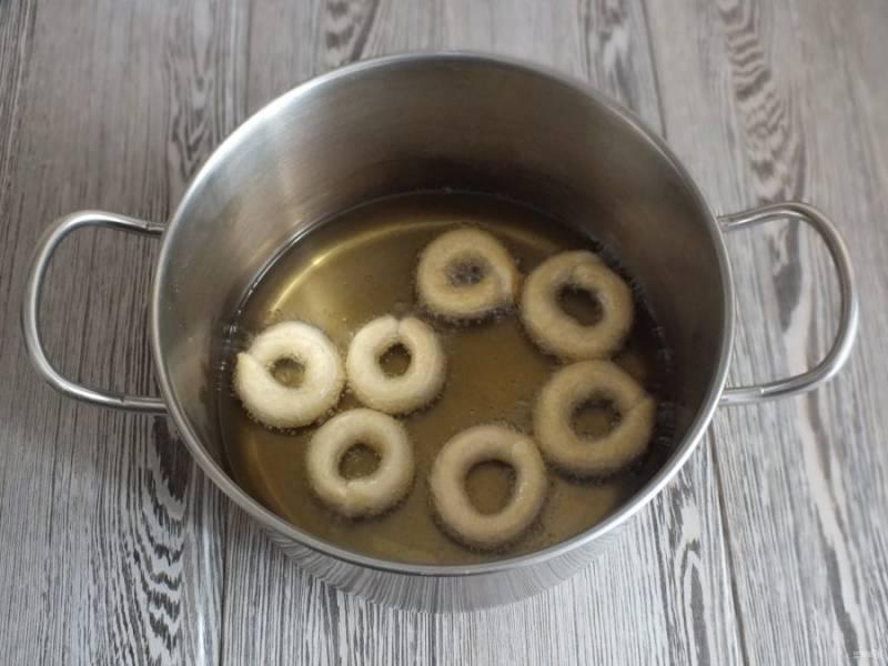 В жаровне или в высокой кастрюле разогрейте растительное масло. Его количество необходимо как для фритюра. Масло не должно быть перекаленным, оптимальный огонь чуть ниже среднего. Опустите в жаровню подготовленные калачики.