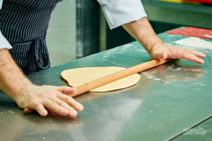 3.В результате тесто получается тугим. Выкладываю его на стол и раскатываю в тонкий пласт.