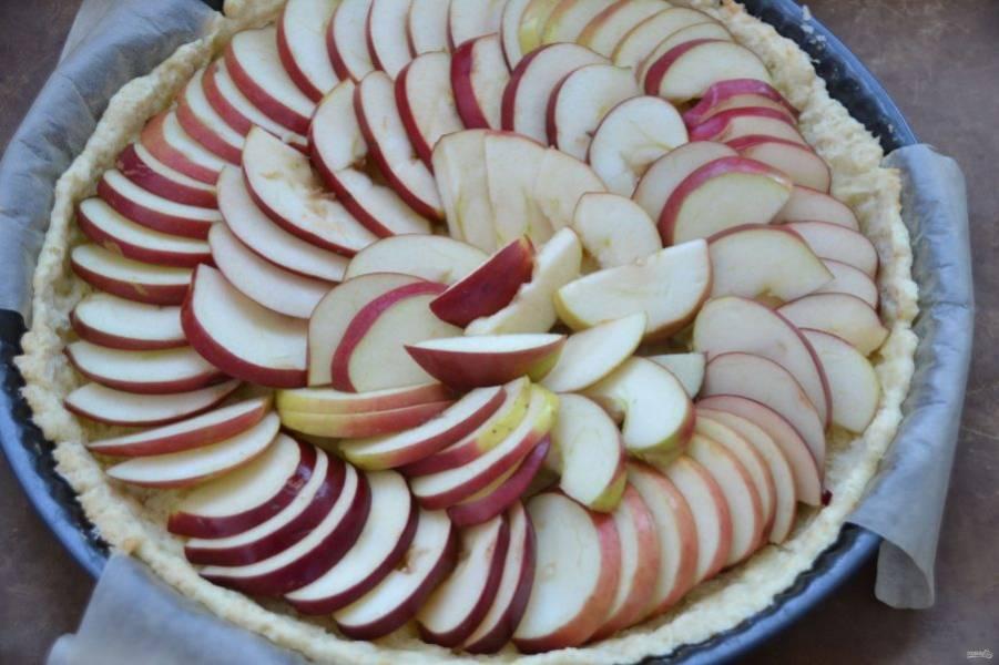 На подпеченную форму выложите яблочные дольки.