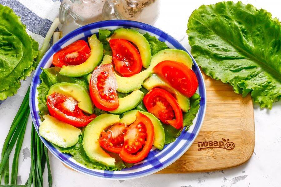 Промойте листовой салат, срежьте стебли и слегка обсушите. Выложите на дно тарелки. Промойте помидор в воде, вырежьте сердцевину и нарежьте ломтиками. Выложите их на салат. Авокадо промойте и разрежьте пополам. Аккуратно удалите кожуру и косточку, нарежьте слайсами и выложите между помидорной нарезки.