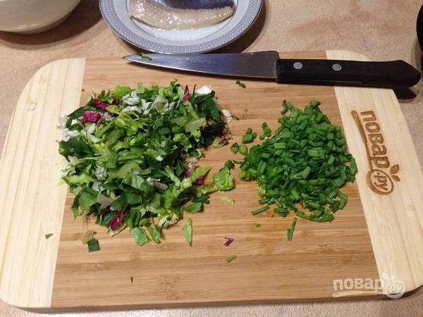 2. Мелко нарезаем листья салата и перья зеленого лука. Выкладываем в салатник.