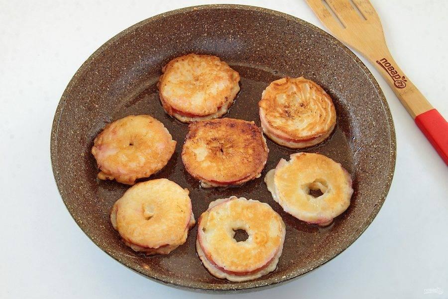 6. Опускаем яблочные кольца в готовое тесто и выкладываем на разогретую сковороду с растительным маслом. Обжариваем на среднем огне с двух сторон до готовности.
