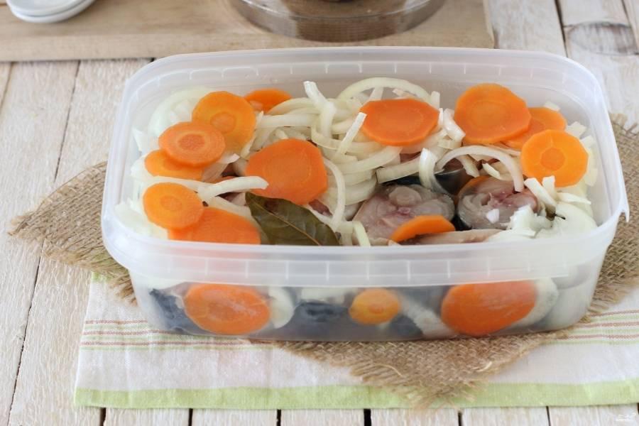 Пока маринад полностью охлаждается, скумбрию порежьте кусочками по 2-4 см. Выложите рыбу в контейнер, переложите её луком и морковкой из маринада.
