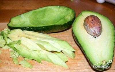 Авокадо разрежьте на 2 половинки. Аккуратно выньте косточку. При помощи ложки или ножа, аккуратно, чтобы не повредить кожицу, выньте мякоть авокадо, нарежьте ее кубиками.