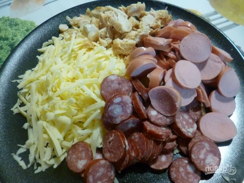 1.Подготовьте начинку: нарежьте кусочками сосиски, охотничьи колбаски, натрите на крупной терке сыр.