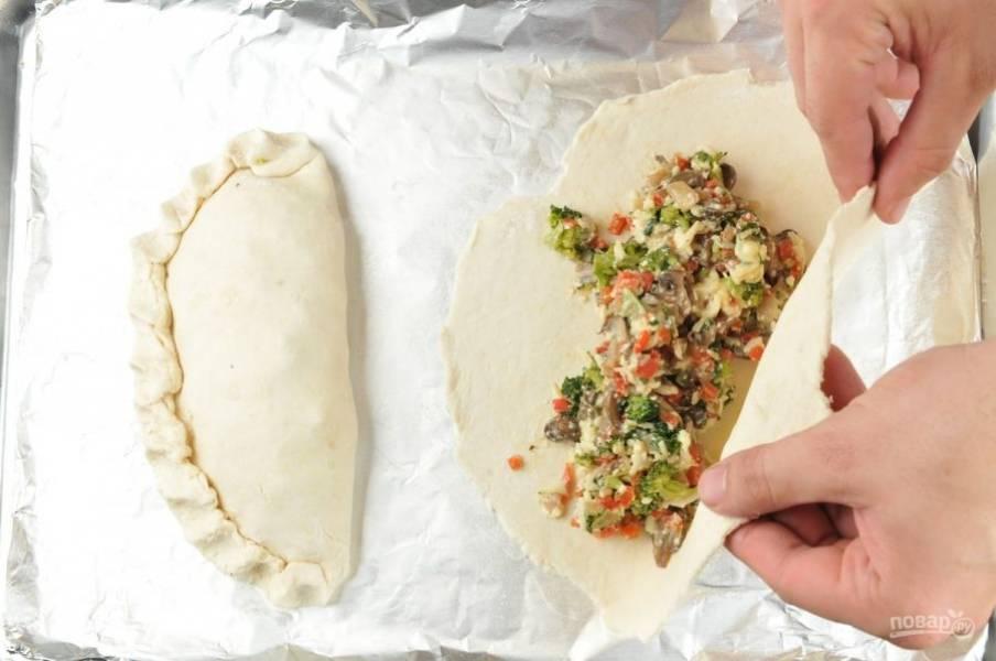 5. На одной части лепёшек распределите начинку. Слепите тесто в виде полумесяца. Сверху смажьте изделия маслом. Отправьте пиццу запекаться на 20 минут в духовку при 200 градусах.