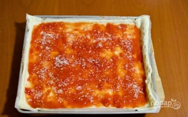 2.На тесто выложите большую часть приготовленного помидорного соуса, посыпьте горстью тертого пармезана.