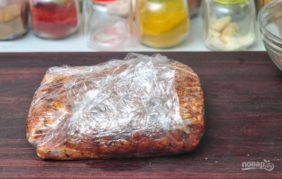 Заверните свиные рёбра в пищевую плёнку. Оставьте их на ночь мариноваться в холодильнике.