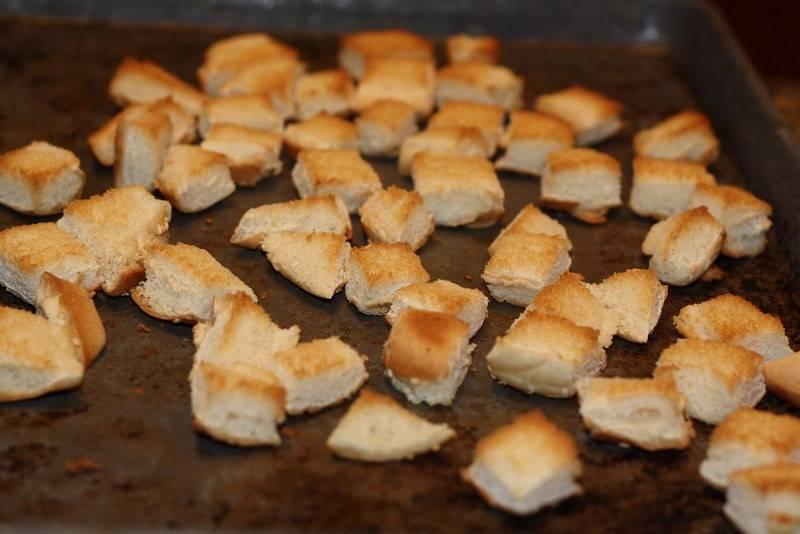 Застилаем противень бумагой для выпечки и выкладываем на нее нарезанный хлеб, ставим его на 5-6 минут в разогретую до 180-200 градусов духовку. Когда хлеб зарумянится и подсохнет, вынимаем его из духовки и ставим остывать.