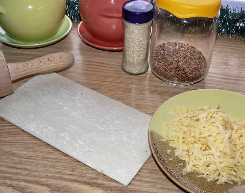 Слоеное тесто выкладываем на стол, посыпаем тертым на крупной терке сыром и раскатываем его немного, чтобы сыр впечатался в тесто.