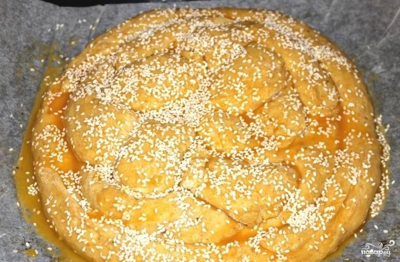 Застилаем противень бумагой для выпечки и перекладываем на нее хлеб. Оставляем на некоторое время, чтобы тесто поднялось. Верхушку смазываем медом и желтком, посыпаем кунжутом. Выпекаем в духовке до румяного состояния. Температура — 220 градусов.