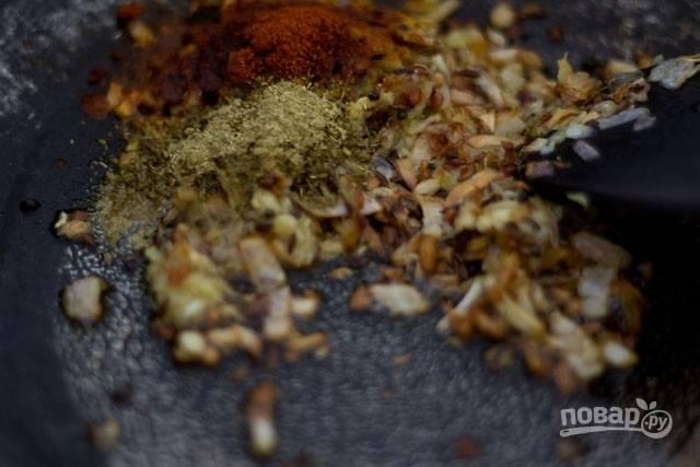 Когда лук обжарится, добавьте специи и измельченные кешью. Обжаривайте несколько минут.