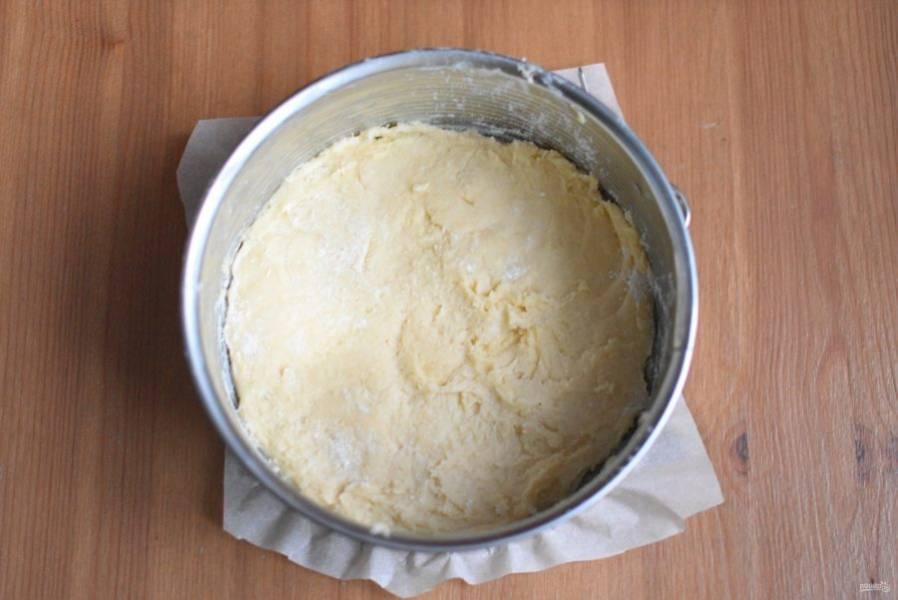 С помощью лопатки выложите тесто в подготовленную форму ровным слоем.