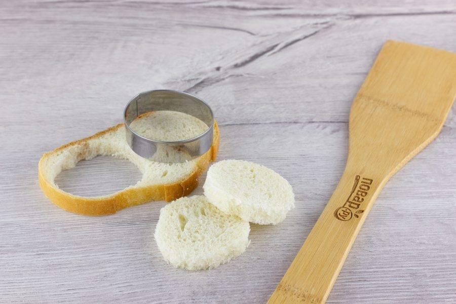 Из хлеба вырежьте кружочки по диаметру формочек для кексов.