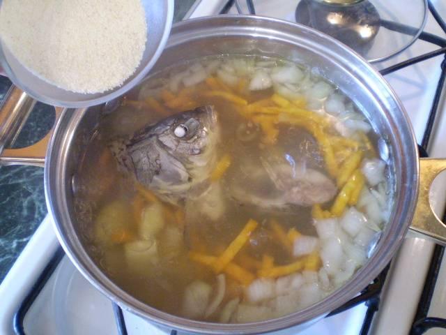 5. Всыпаем тонкой струйкой манную крупу и постоянно мешаем суп, чтобы манка не взялась комочками. Варим еще 5 минут.