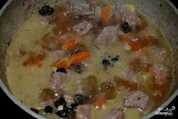 Через положенное время закладываем промытые сухофрукты в сковородку с мясом. Все перемешиваем и тушим еще минут 30-40.