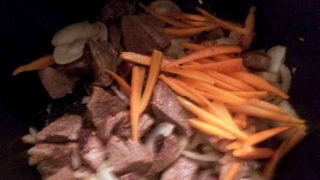 Солим и перчим мясо, добавляем любые специи по вкусу. Морковь режем соломкой, а лук - полукольцами. Добавляем к мясу.