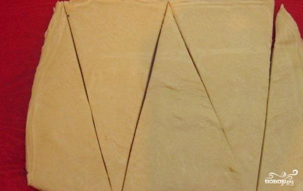 Тесто разморозьте заранее. Раскатайте его толщиной в 3 мм. Нарежьте треугольниками с основанием в 5 см, а высотой примерно в 10.