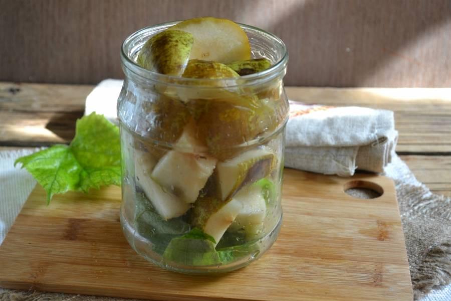 На дно чистой простерилизованной банки положите промытые виноградные листья. Сложите кусочки груш как можно плотнее.