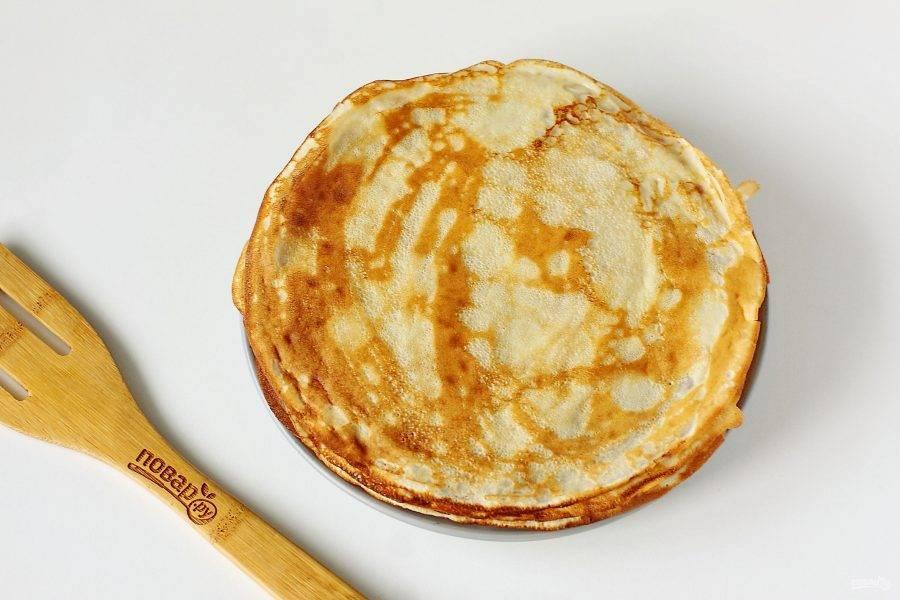 Готовые блины на кефире с содой складывайте стопочкой и по желанию смазывайте кусочком сливочного масла.