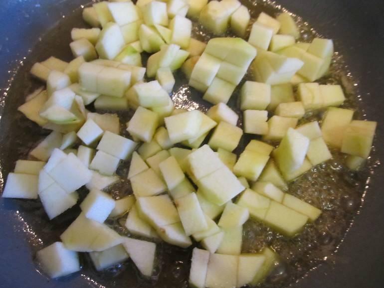 3. На сковороде растопите ложку сливочного масла. Добавьте около 2 ложек воды и сахар по вкусу. Доведите до кипения. Тем временем очистите от кожицы и семян яблоко, нарежьте небольшими кубиками. Добавьте в карамель, аккуратно перемешайте. Обжарьте пару минут, а затем оставьте в сковороде еще минут на 5.