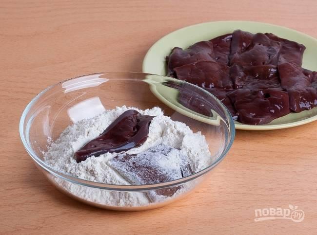 1.Мою печень и заливаю кипятком, затем сразу же перекладываю в холодную воду. Снимаю кожуру и нарезаю печень кусочками толщиной 1 сантиметр. Солю ее и обваливаю в муке.