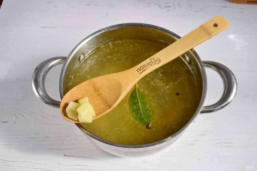 Бульон доведите до кипения. Добавьте лавровый лист, перец душистый горошком и картофель, нарезанный кубиками. Варите на медленном огне до мягкости.