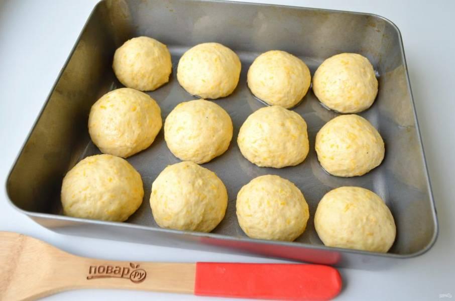9. Смажьте противень растительным маслом. Стол и руки тоже смажьте маслом. Разделите тесто на 12 частей. Сформируйте булочки, расположите их на небольшом расстоянии. Поставьте булочки в теплую духовку на 20 минут для подъема. Включите духовку на 180 градусов и выпекайте булочки 25-30 минут.
