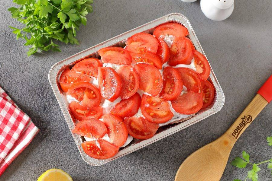 Полейте все сметаной и сверху разложите нарезанные дольками помидоры. Помидоры посолите и поперчите по вкусу.