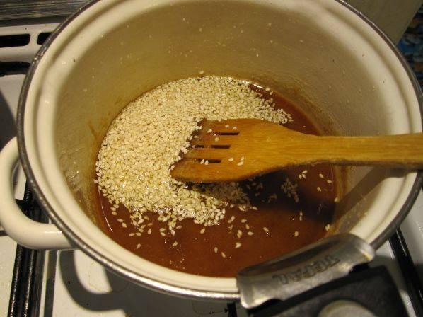 8. В уже жидкую карамель добавить кунжут, быстро перемешать и можно поливать готовой карамелью яблоки.