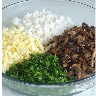 Сыр натираем на средней терке, зелень мелко рубим. Выкладываем в одно блюдо сыр, зелень, рис и грибы.