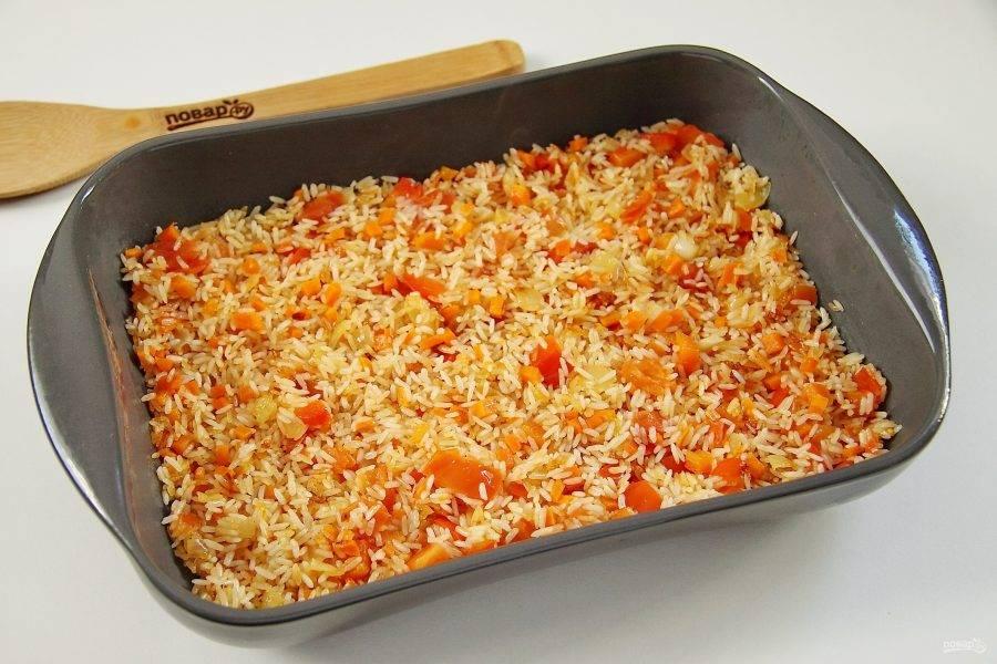 В форму для запекания выкладываем слой риса с овощами.