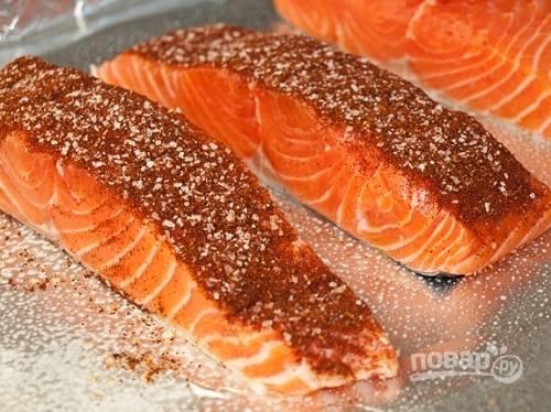 Застилаем противень фольгой и смазываем маслом. Выкладываем рыбу кожей на противень и равномерно посыпаем смесью специй.