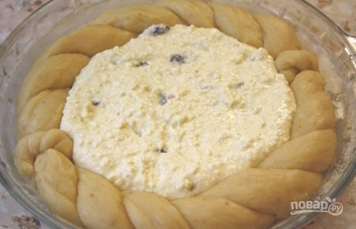 Когда тесто увеличится в два раза, разделите его на две части. Из первой раскатайте круг и выложите его в форму для запекания. Затем из второй части сделайте плетенку и выложите ее так, чтобы получился бортик. В углубление выложите начинку.