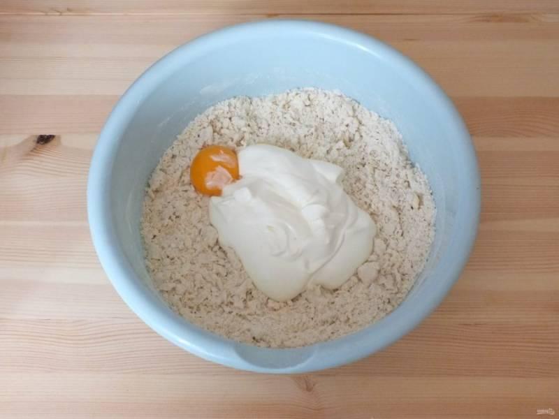 К крошке добавьте желток, сметану. Замесите мягкое, пластичное тесто. Долго не месите. Скаталось в комок, достаточно.