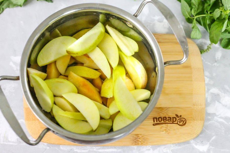 Яблоки промойте в воде, разрежьте на четвертинки и срежьте семенные блоки. Если на кожуре фруктов есть парафин, то обязательно срежьте ее. Промойте четвертинки и нарежьте их ломтиками в кастрюлю, в которой собираетесь варить компот. Точно так же очистите и нарежьте айву.