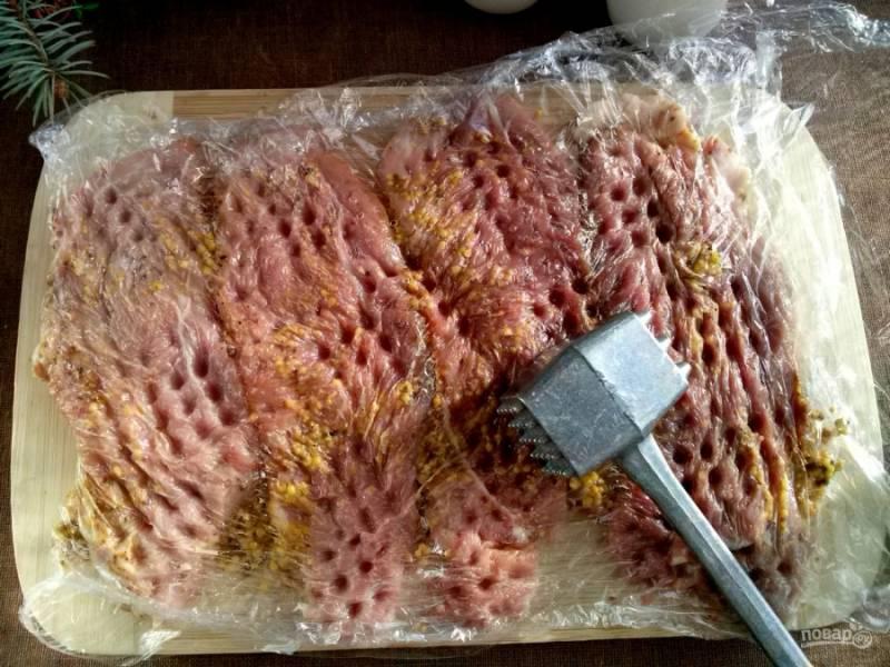 Накройте мясо пищевой пленкой и отбейте молоточком так, чтобы мясо не порвалось. Оставьте мариноваться на 15 минут.