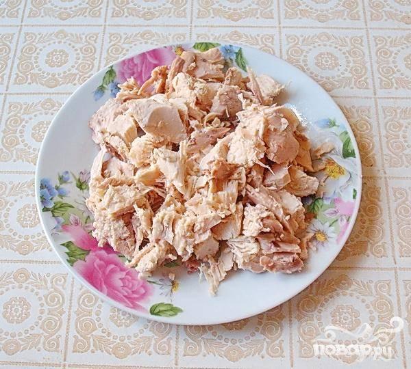 1.Промываем куриную грудинку и минут на сорок пять-пятьдесят ставим ее отвариваться с лавровым листом и перцем, добавим туда еще корешки и луковицу.  Когда мясо сварится, даем ему остыть прямо в бульоне, а затем очистим от кожицы и отделим мясо от костей. Крупными кубиками нарезаем мясо.