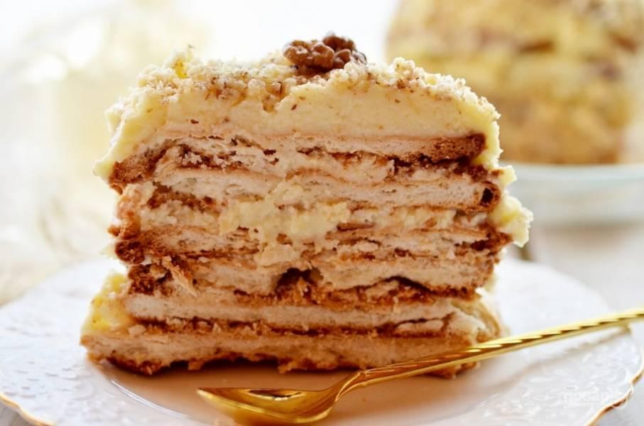 После того, как пирожное спрессовалось, смажьте кремом верхний слой и бока, посыпьте измельчёнными орехами и снова поместите на холод для пропитки.