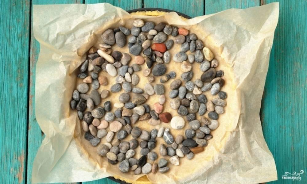 Разогрейте духовку до 200 градусов. Тесто распределите по форме для выпечки, сверху уложите пергаментную бумагу. Выложите груз (например, небольшие камушки). Как тесто прижмётся, убирайте груз и ставьте форму в духовку на 20 минут. Но можно ставить тесто в духовку и с грузом.