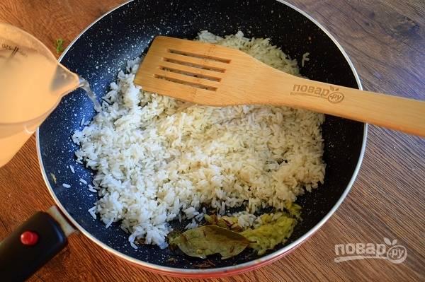 Высыпьте промытый, обсушенный рис. Добавьте соль и горячую воду так, чтобы она покрывала рис на палец сверху. Закройте крышкой, доведите до кипения и варите на медленном огне до выпаривания воды.