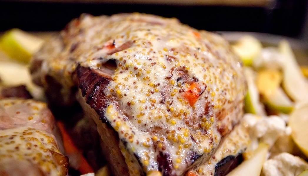 Спустя сорок минут смажьте мясо заранее подготовленным горчичным соусом и обложите порезанными на четверти ломтиками яблок и груш, крупными кусочками ананаса и зонтиками цветной капусты. Фрукты выкладываем поверх ранее уложенных картофеля и лука, чтобы они постепенно пропитывали их своим соком. И ставим блюдо обратно в духовку еще на 30-40 минут.