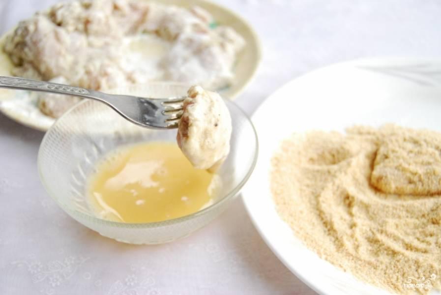 В плоскую тарелку высыпьте панировочные сухари. Обмакните кусочек курицы сначала в яйце, затем изваляйте в панировочных сухарях.