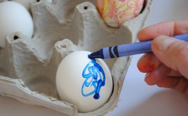 3. Когда яйца сварились вкрутую, воду с них нужно слить, но не остужать их. Выставить на рабочую поверхность и тут же приступить к работе. Восковые мелки при контакте с еще теплым яйцом плавятся и дают просто великолепные разводы. Для детей яйцо лучше немного остудить, так как есть вероятность обжечь руки.