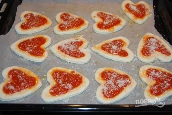 7.Смажьте томатным соусом мини-пиццы, посыпьте тертым пармезаном и выпекайте предварительно разогретой до 180 градусов духовке в течение 10 минут.