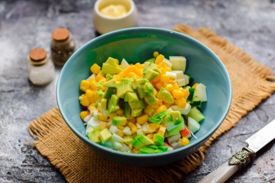 Добавьте в салат кукурузу и нарезанный кубиками авокадо.